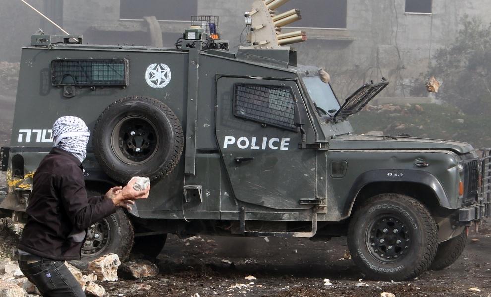 12. ZACHDONI BRZEG, 25 stycznia 2013: Palestyńczyk rzuca kamieniem w kierunku policyjnego samochodu. AFP PHOTO/JAAFAR ASHTIYEH