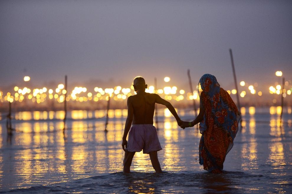 11.INDIE, Allahabad, 8 lutego 2013: Kobieta i mężczyzna przygotowują się do rytualnej kąpieli w dorzeczu Gangesu. AFP PHOTO/ROBERTO SCHMIDT