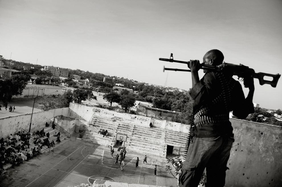 """13.SOMALIA, Mogadiszu, 21 lutego 2012: Pierwsze miejsce w kategorii """"Sports Feature Stories"""". Uzbrojony strażnik pilnuje bezpieczeństwa kobiet grających w   koszykówkę. Kobiety te ryzykują życiem, ponieważ gra w koszykówkę nie jest aprobowana przez radykalnych islamistów. AFP PHOTO/ LAIF / Jan Grarup"""