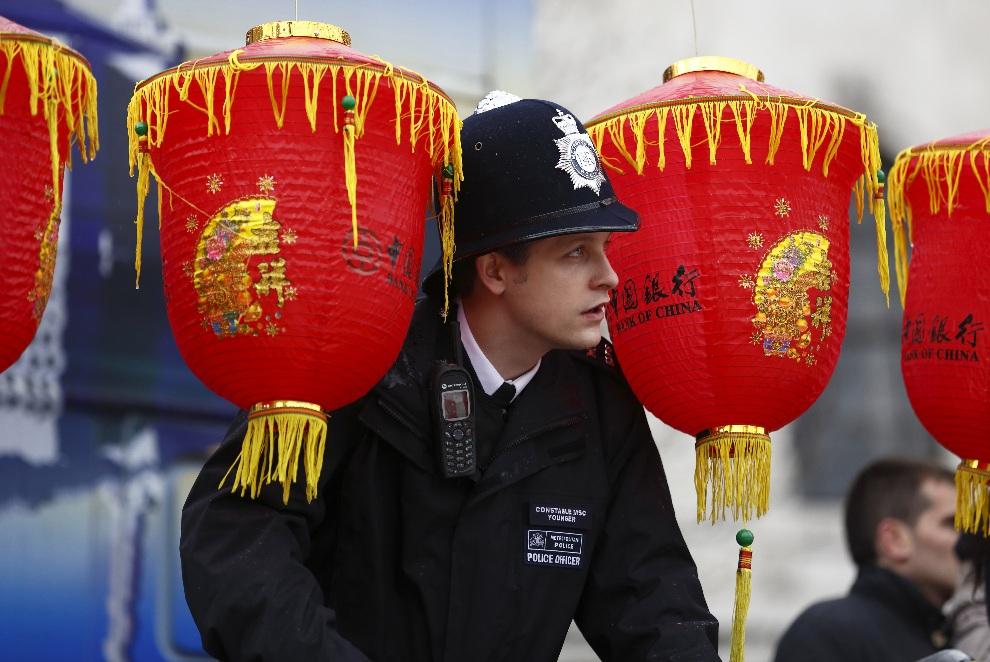 14.WIELKA BRYTANIA, Londyn, 10 lutego 2013:Policjant między dekoracjami uświetniającymi obchody Nowego Roku Księżycowego. AFP PHOTO / JUSTIN TALLIS