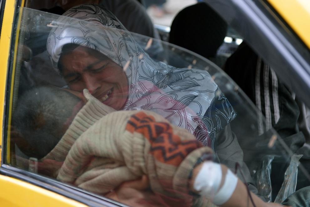 18.SYRIA, Aleppo, 8 lutego 2013: Kobieta wioząca w taksówce ranne dziecko. AFP PHOTO/AAMIR QURESHI