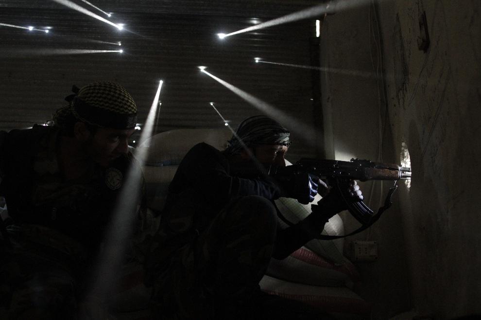 2.SYRIA, Aleppo, 19 października 2012: Syryjscy rebelianci przyjmują pozycje strzeleckie w jednym z budynków dzielnicy Karmal Jabl. AFP PHOTO/JAVIER MANZANO