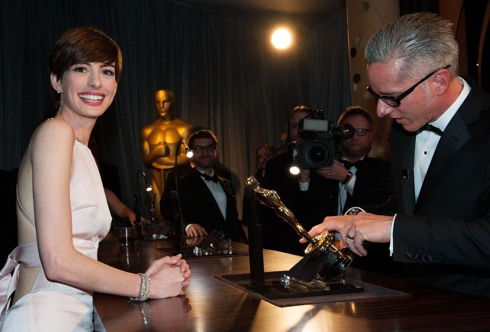 34.USA, Hollywood, 24 lutego 2013: Actress Anne Hathaway przygląda się grawerowi pracującemu z jej Oscarem. AFP PHOTO/VALERIE MACON