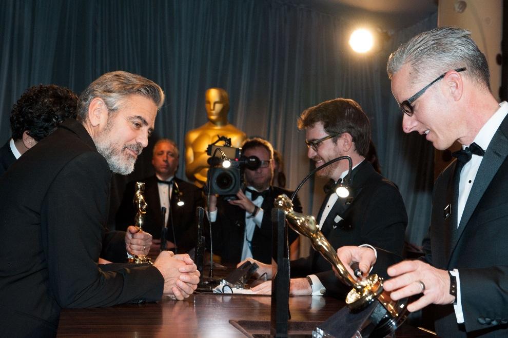 35.USA, Hollywood, 24 lutego 2013: George Clooney przygląda się grawerowi pracującemu z jego Oscarem. AFP PHOTO/VALERIE MACON