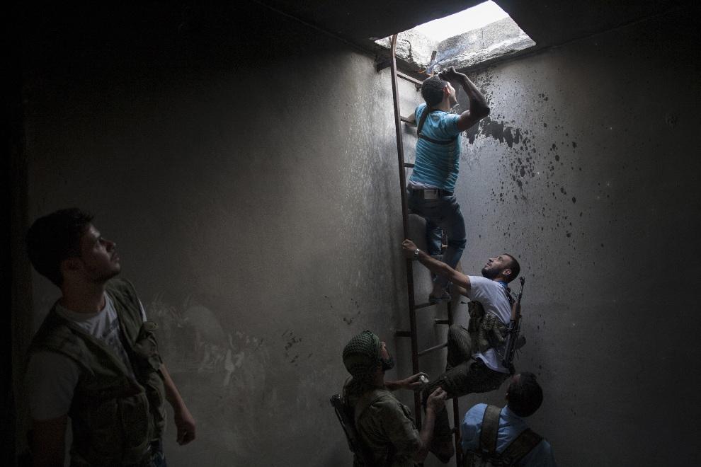 3.SYRIA, Aleppo, 20 października 2012: Rebeliant przygotowuje się do rzucenia przez właz granatu domowej produkcji. AFP PHOTO/FABIO BUCCIARELLI