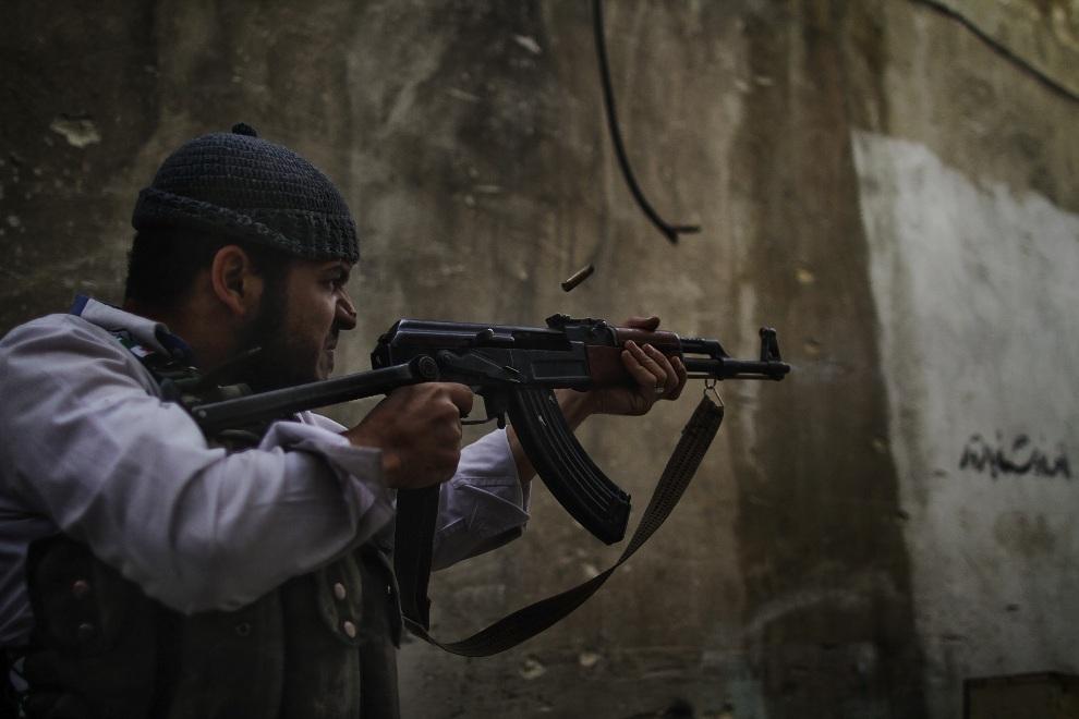 4.SYRIA, Aleppo, 24 października 2012: Rebeliant ostrzeliwuje pozycje oddziałów rządowych. AFP PHOTO / JAVIER MANZANO