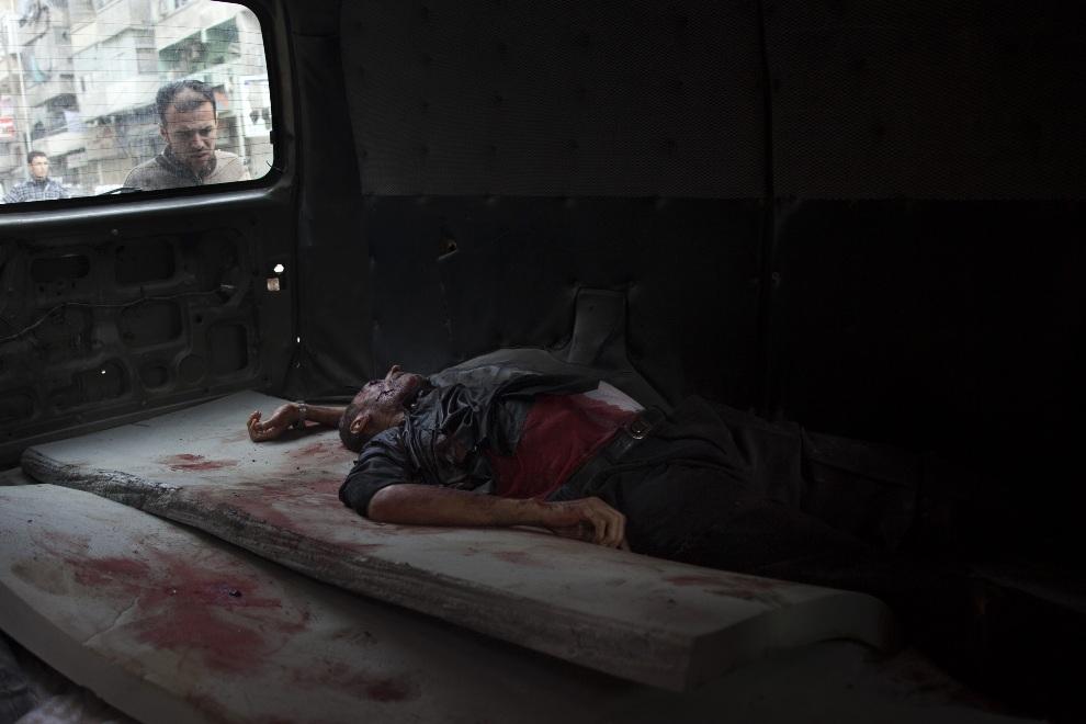 9.SYRIA, Aleppo, 21 października 2012: Ciało mężczyzny leżące w furgonetce. AFP PHOTO/FABIO BUCCIARELLI
