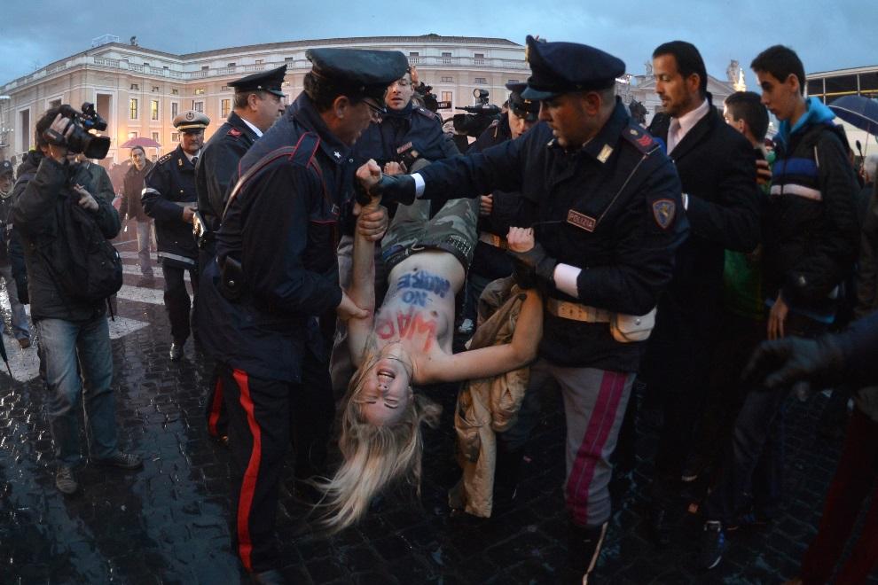 12.WŁOCHY, Rzym, 12 marca 2013: Aktywistka grupy Femen aresztowana przez policjantów. AFP PHOTO / GABRIEL BOUYS