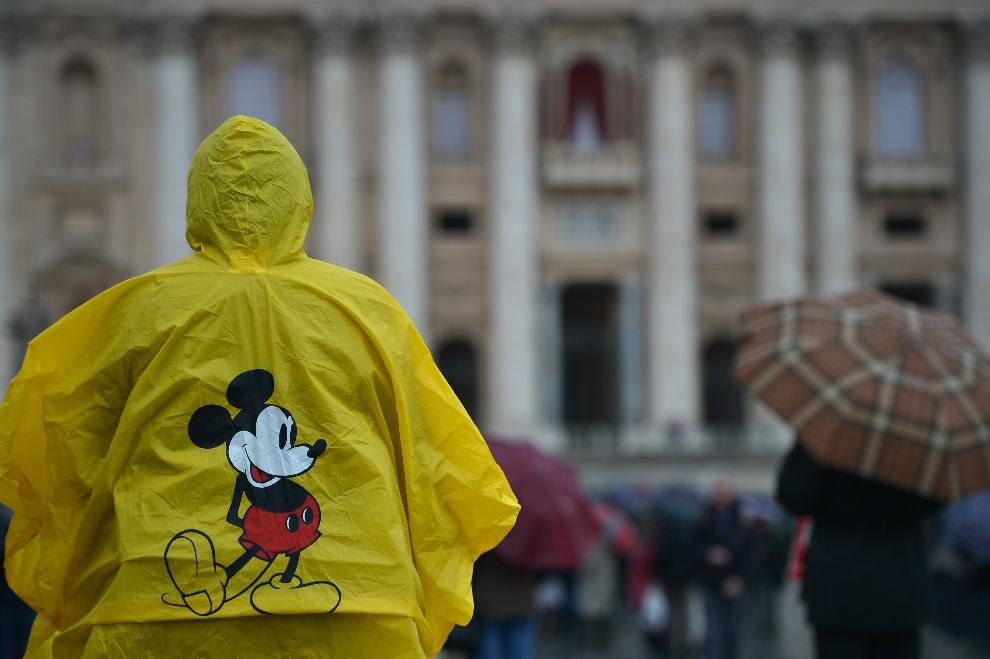 14.WATYKAN, 12 marca 2013: Mężczyzna w pelerynie na placu św. Piotr. AFP PHOTO / GABRIEL BOUYS