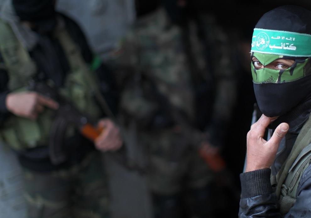 14.STREFA GAZY, 17 marca 2013: Członek Hamasu uczestniczący w pogrzebie Mariama Farahata. AFP PHOTO MAHMUD HAMS