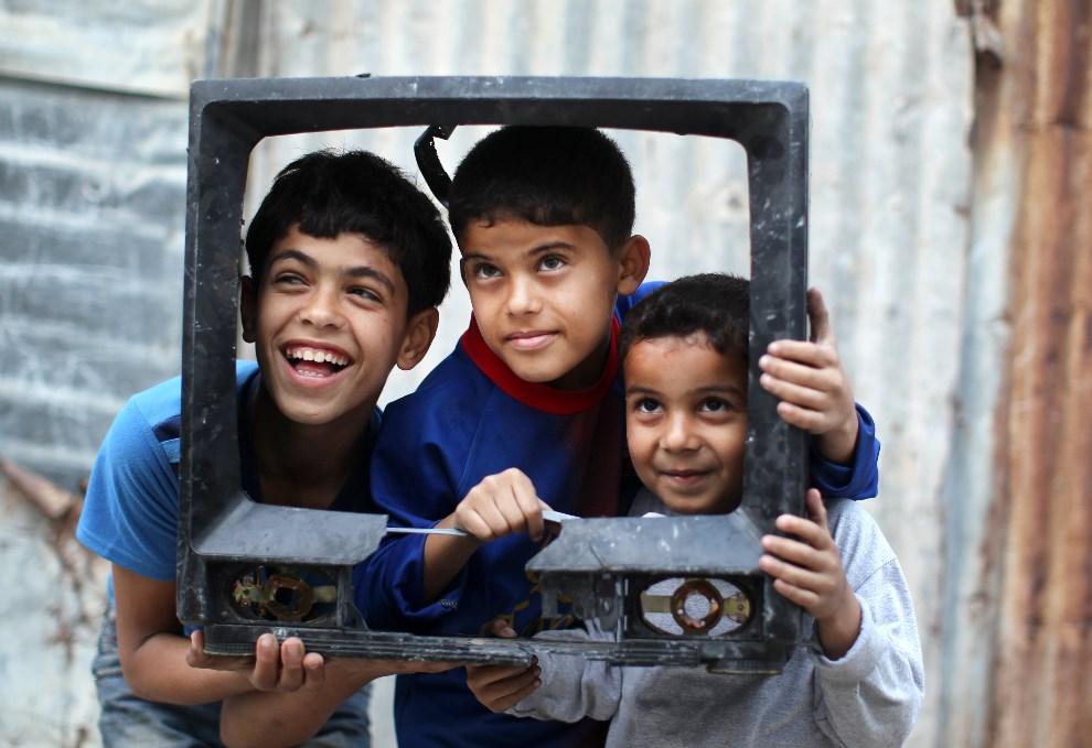 15.STREFA GAZY, 13 marca 2013: Palestyńscy chłopcy bawią się zniszczonym telewizorem.  AFP PHOTO / MAHMUD HAMS