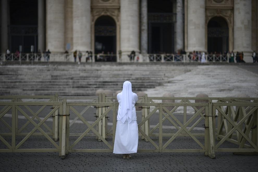 16.WATYKAN, 12 marca 2013: Zakonnica modląca się przed bazyliką św. Piotra. AFP PHOTO / JOHANNES EISELE