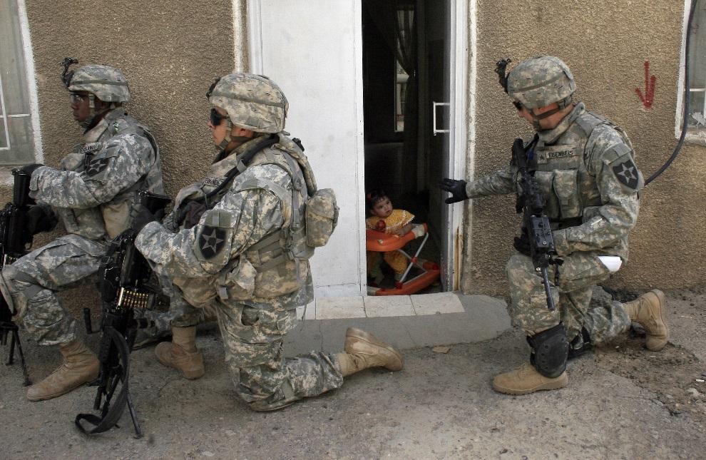 16.IRAK, Bagdad, 21 kwietnia 2007: Amerykański żołnierz podczas patrol pozdrawia mała dziewczynkę. AFP PHOTO/WISSAM AL-OKAILI