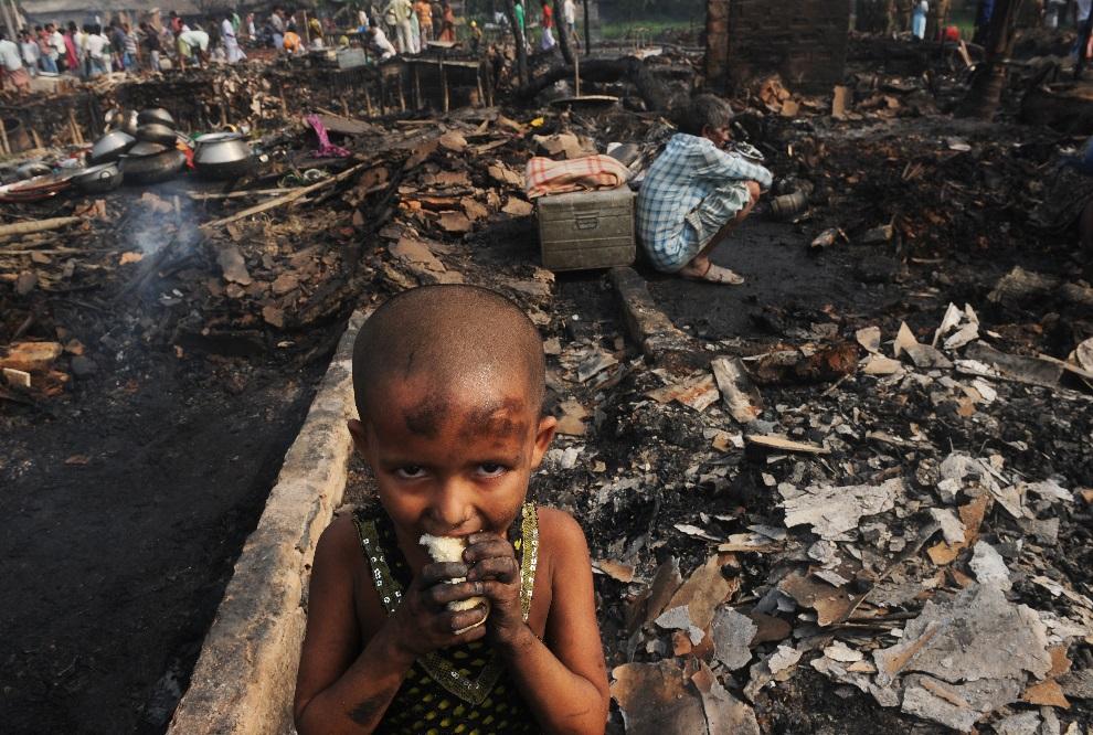 17.INDIE, Kolkata, 16 marca 2013: Dziewczynka na zgliszczach swojego domu w podmiejskich slamsach. AFP PHOTO/ Dibyangshu SARKAR