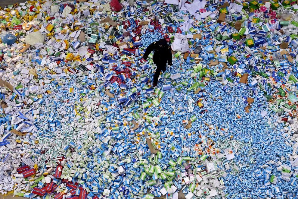 17.CHINY, Pekin, 14 marca 2013: Policjant na stercie podrabianych leków zarekwirowanych przez władze.  AFP PHOTO