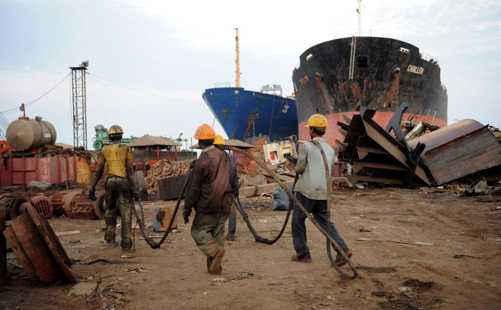 18.INDIE, Alang, 27 maja 2011: Mężczyźni zatrudnieni przy złomowaniu statków. AFP PHOTO / Sam PANTHAKY