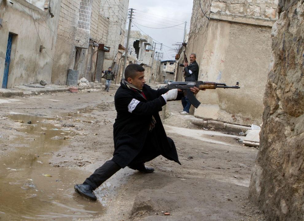 20.SYRIA, Aleppo, 4 marca 2013: Mężczyzna ostrzeliwuje pozycje wojsk rządowych. AFP PHOTO/STEPHEN J. BOITANO
