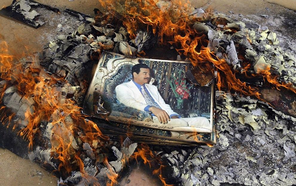 20.IRAK, Qalat Sukkar, 7 kwietnia 2003: Palące się zdjęcia z wizerunkiem Saddama Husseina. (Foto:  Chris Hondros/Getty Images)