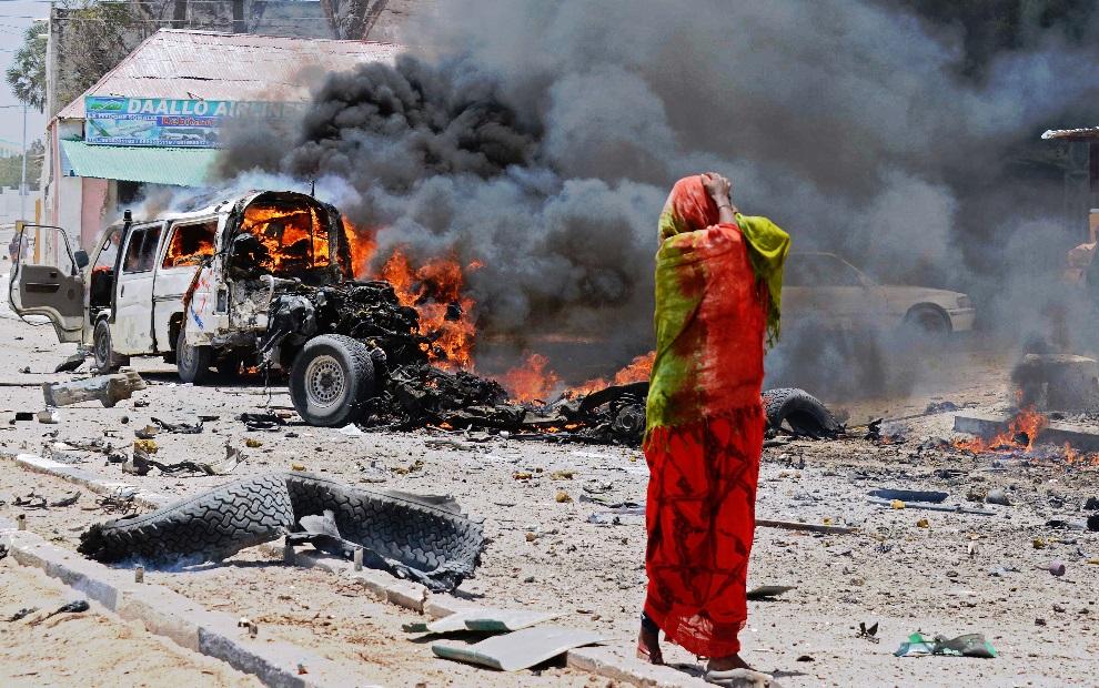 21.SOMALIA, Mogadiszu, 18 marca 2013: Kobieta stojąca w pobliżu miejsca eksplozji bomby w centrum miasta.  AFP PHOTO/Mohamed Abdiwahab