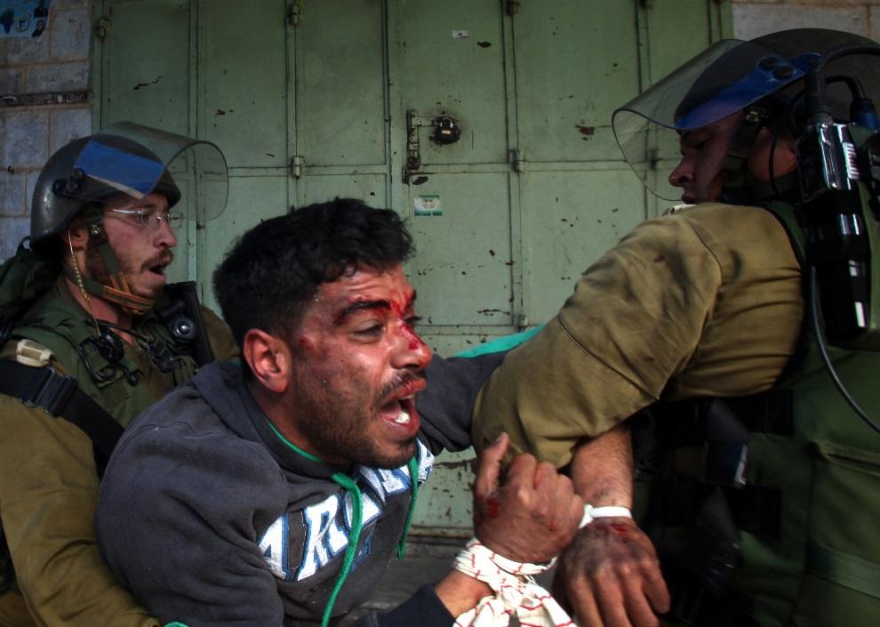22.ZACHODNI BRZEG, Hebron, 1 marca 2013: Palestyńczyk zatrzymany podczas starć z żołnierzami. AFP PHOTO / HAZEM BADER