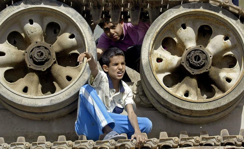 22.IRAK, Basra, 20 marca 2006: Chłopcy bawiący się na zniszczonym czołgu. AFP PHOTO/ESSAM AL-SUDANI