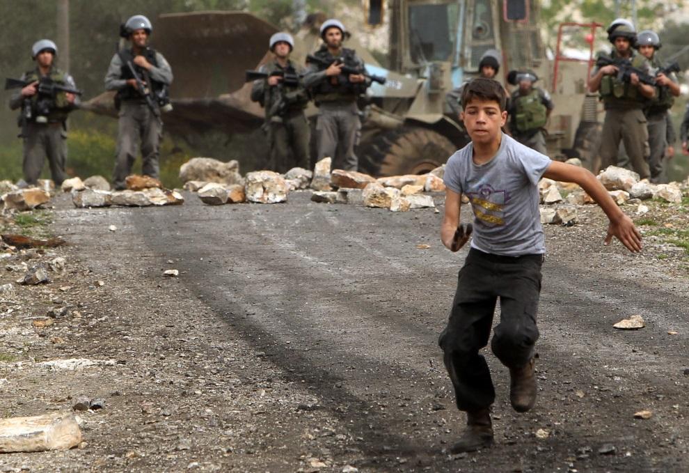 23.ZACHODNI BRZEG, 8 marca 2013: Palestyńczyk ucieka przed żołnierzami. AFP PHOTO/JAAFAR ASHTIYEH
