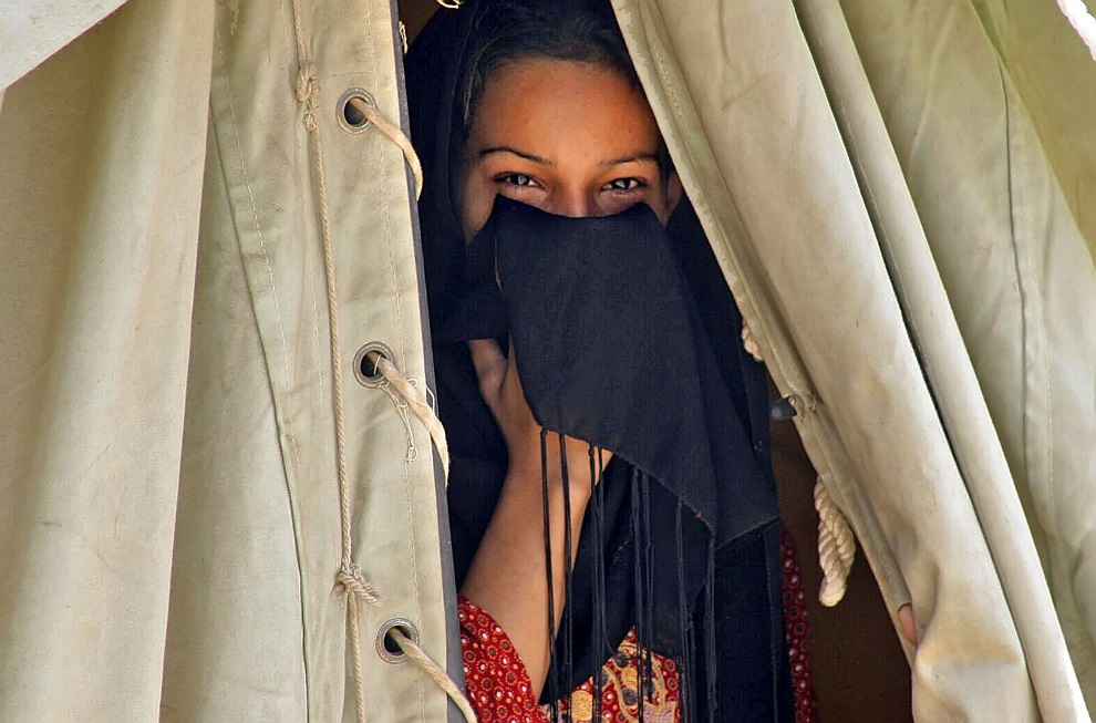 24.IRAK, Diwanijja, 3 kwietnia 2006: Dziewczyna zasłaniająca twarz u wejścia do namiotu w prowizorycznym miasteczku dla uchodźców. AFP PHOTO/QASSEM ZEIN