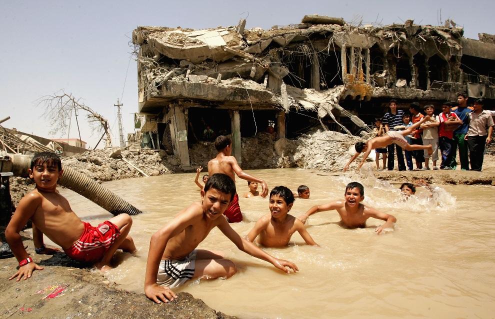 26.IRAK, Bagdad, 20 maja 2008: Chłopcy pływają w leju po eksplozji wypełnionym wodą. (Foto:  Wathiq Khuzaie /Getty Images)