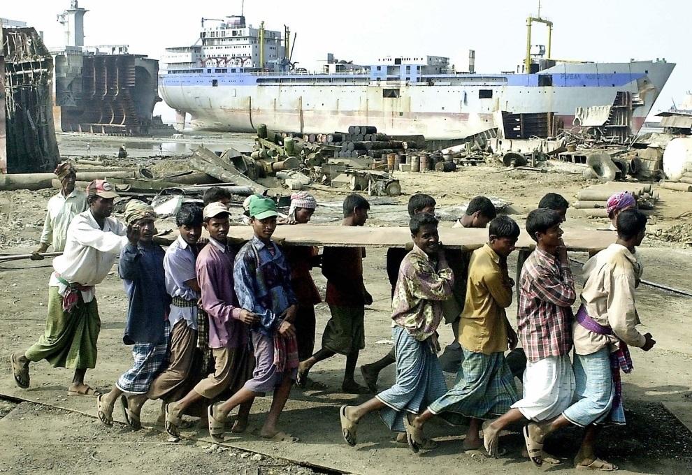 28.BANGLADESZ, Chittagong, 21 grudnia 2004: Mężczyźni przenoszą fragment stalowej płyty odciętej ze złomowanego statku. AFP PHOTO/Farjana K. GODHULY