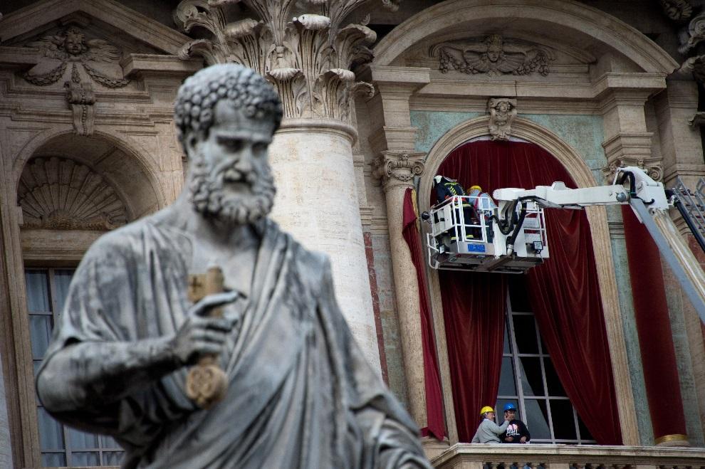 29.WATYKAN, 11 marca 2013: Dekorowanie balkonu przy bazylice św. Piotra. AFP PHOTO / JOHANNES EISELE