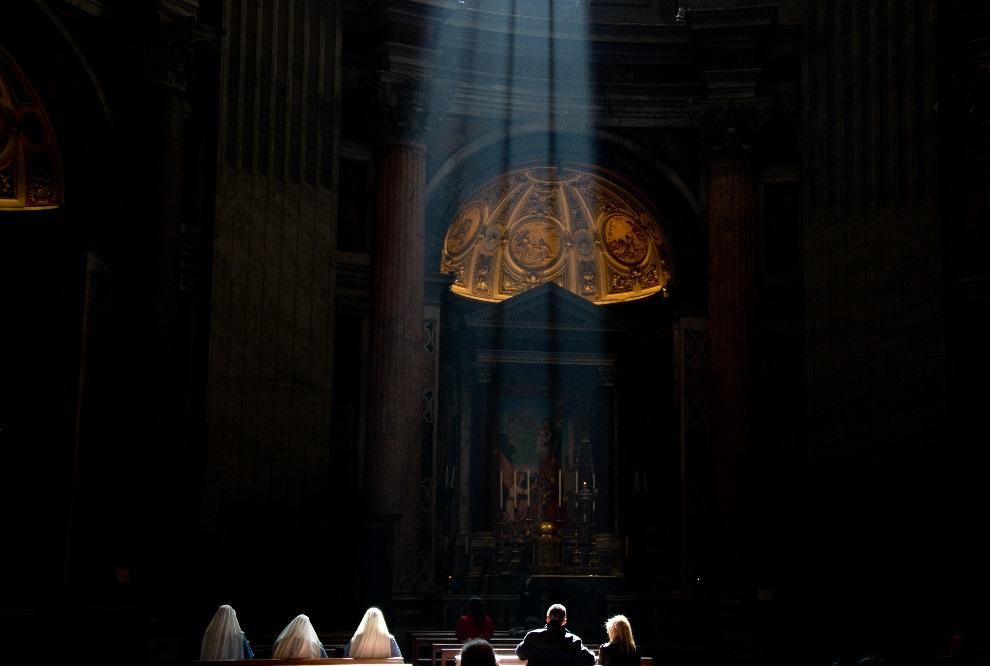 2.WATYKAN, 10 marca 2013: Zakonnice modlące się we wnętrzu bazyliki św. Piotra. AFP PHOTO / JOHANNES EISELE