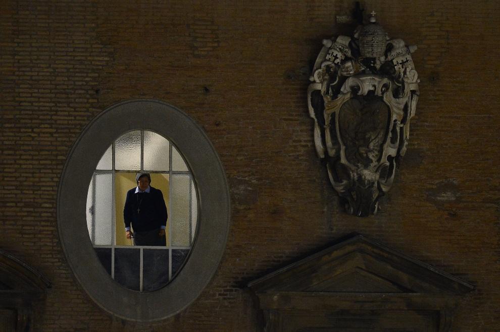 32.WATYKAN, 13 marca 2013: Zakonnica spoglądająca z okna na plac św. Piotra w chwilę po ukazaniu się białego dymu. AFP PHOTO / GIUSEPPE CACACE