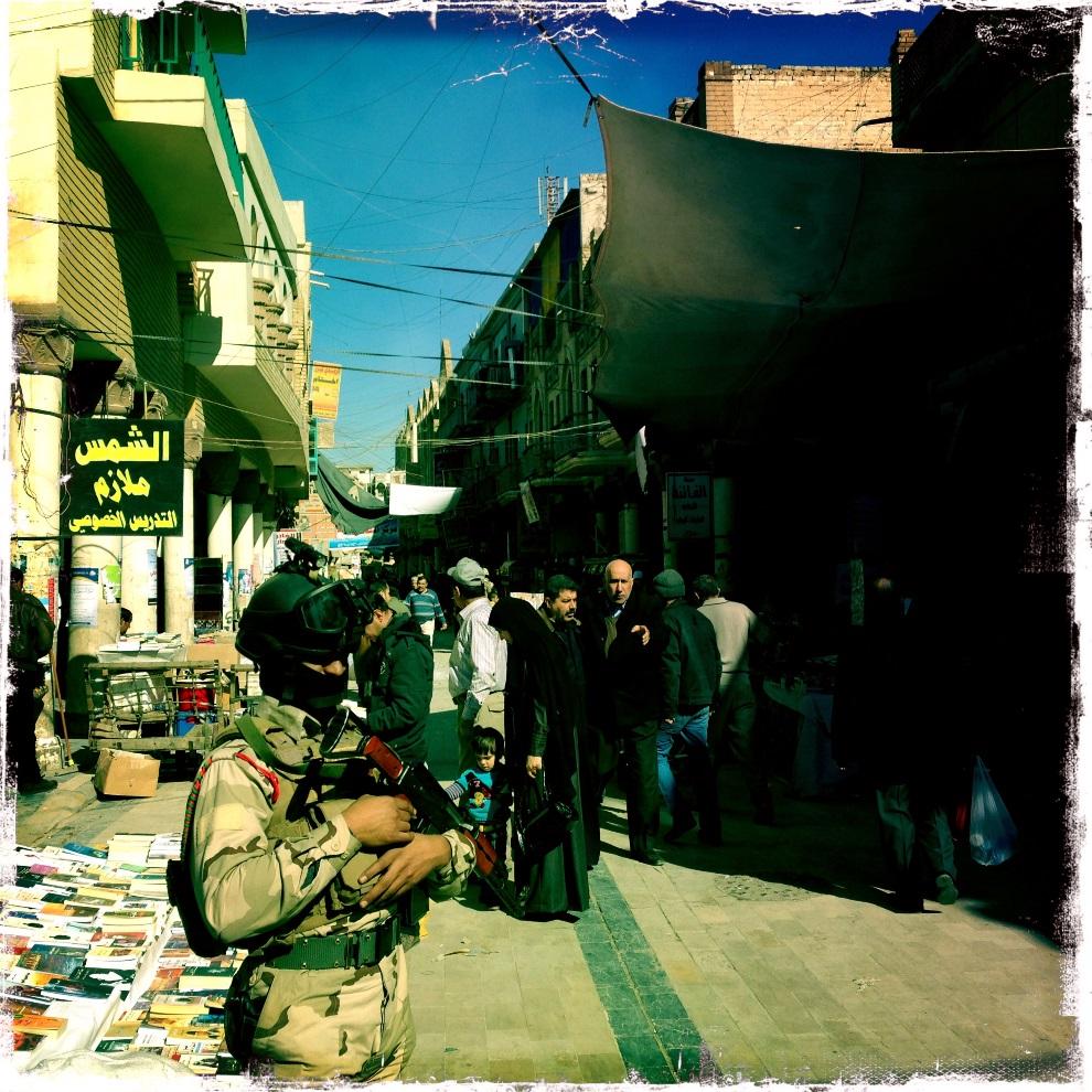 35.IRAK, Bagdad, 3 lutego 2013: Policjant pilnujący porządku na ulicy Al-Mutanabi. AFP PHOTO / PATRICK BAZ