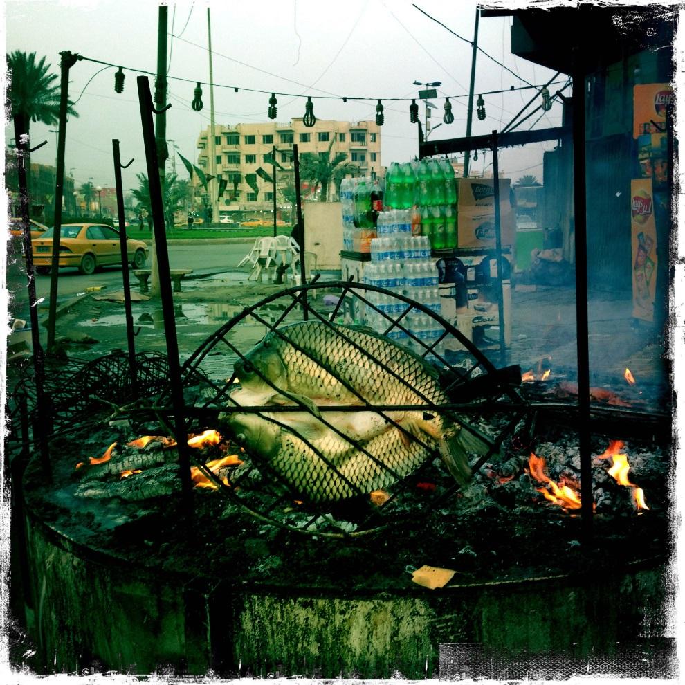 37.IRAK, Bagdad, 7 lutego 2013: Karp pieczony nad żarem. AFP PHOTO / PATRICK BAZ