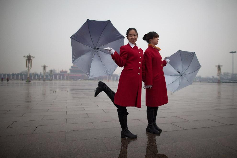4.CHINY, Pekin, 12 marca 2013: Hostessy na placu Tiananmen czekają na delegatów wracających z sesji Ludowej Politycznej Konferencji Konsultatywnej Chin. AFP PHOTO / Ed Jones