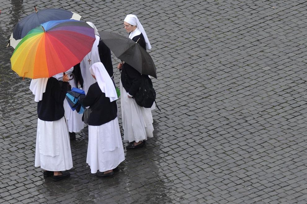 8.WATYKAN, 13 marca 2013: Zakonnice pod parasolami chronią się przed deszczem. AFP PHOTO / TIZIANA FABI