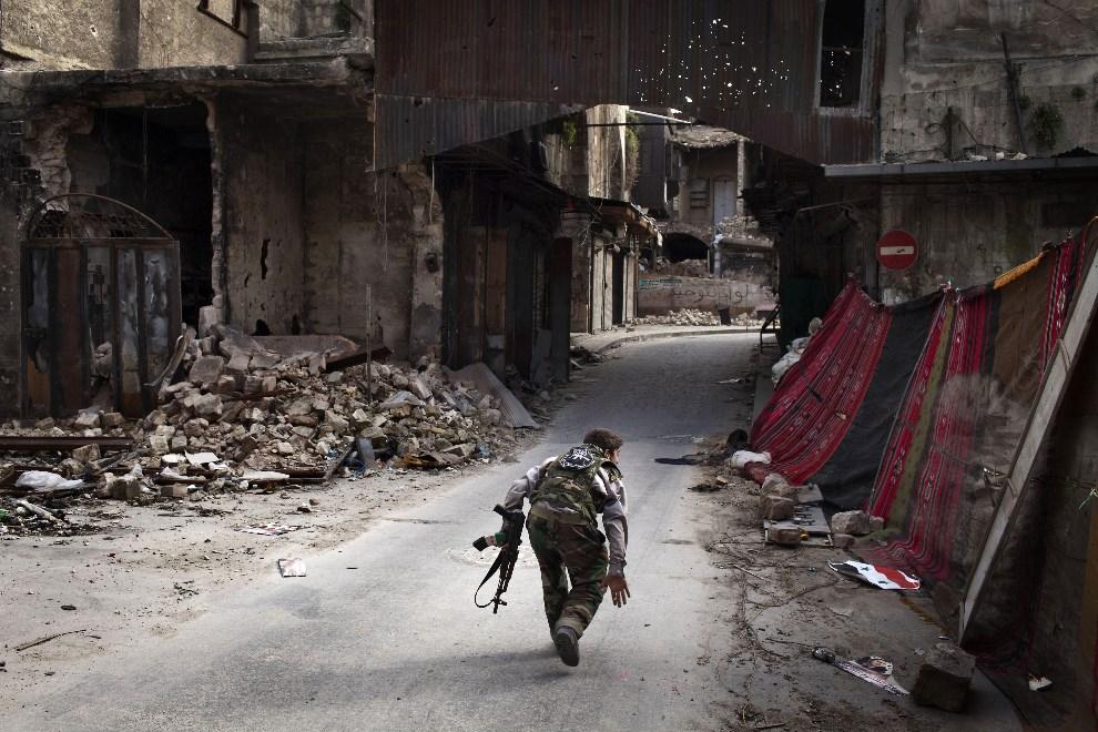 8.SYRIA, Aleppo, 11 marca 2013: Rebeliant chroniący się przed ogniem snajpera. AFP PHOTO/JM LOPEZ