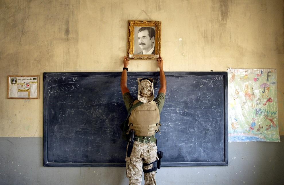 8.IRAK, Al-Kut, 16 kwietnia 2003: Marine zdejmuje portret Saddam Husseina zawieszony w szkole. (Foto:  Chris Hondros/Getty Images)