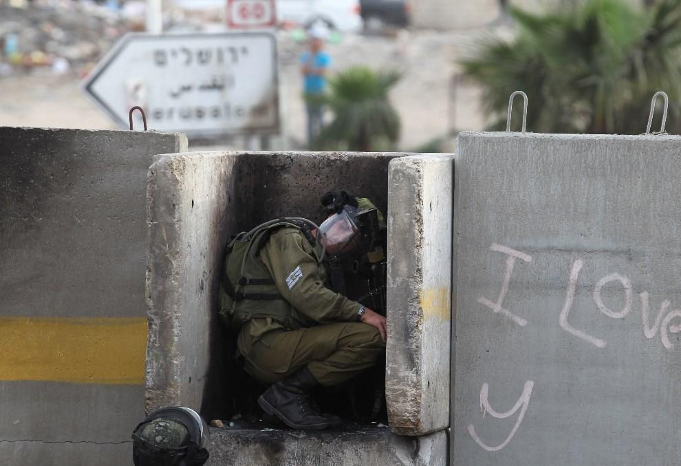 9.ZACHODNI BRZEG, Ar-Ram, 15 marca 2013: Izraelski żołnierz w trakcie starć z uczestnikami pogrzebu mężczyzny, ofiary jednej z demonstracji. AFP PHOTO/ABBAS MOMANI