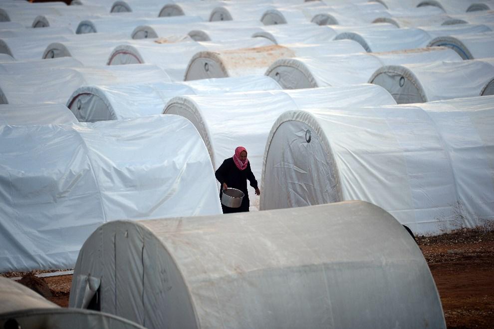 11.SYRIA, Azaz, 17 kwietnia 2013: Mężczyzna idący między namiotami w obozie dla uchodźców. AFP PHOTO / DIMITAR DILKOFF