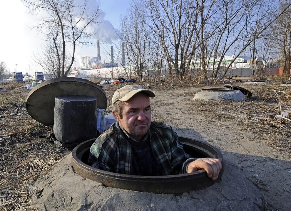 12.POLSKA, Warszawa, 2 lutego 2012: Bezdomny wychodzi ze studzienki ciepłociągu. AFP PHOTO / JANEK SKARZYNSKI