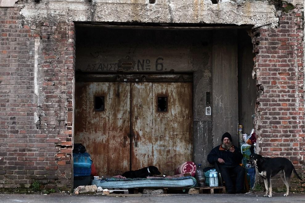 """13.GRECJA, Ateny, 6 lutego 2013: Bezdomny """"mieszkający"""" w porcie. AFP PHOTO / ARIS MESSINIS"""