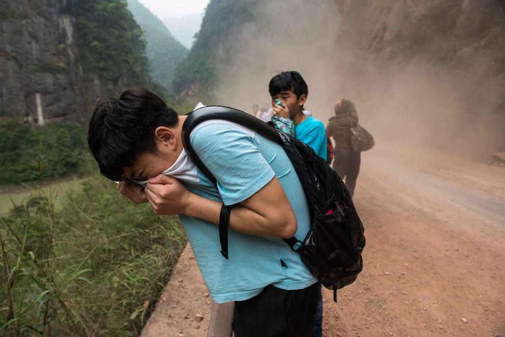 13.CHINY, Ya'an, 21 kwietnia 2013: Ludzie zasłaniają twarze chroniąc się przed unoszącym się kurzem.  AFP PHOTO