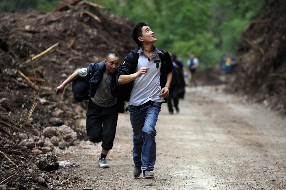 14.CHINY, Ya'an, 21 kwietnia 2013: Ludzie uciekający przed spadającymi głazami podczas wstrząsów wtórnych. AFP PHOTO