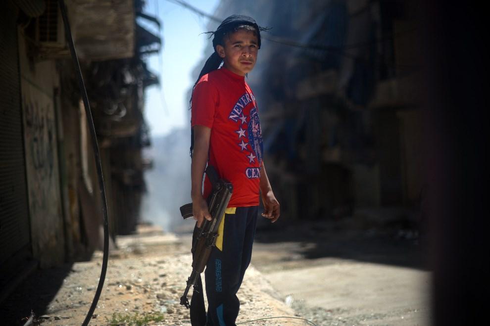 14.SYRIA, Aleppo, 14 kwietnia 2013: Chlopiec z karabinem AK-47. AFP PHOTO / DIMITAR DILKOFF
