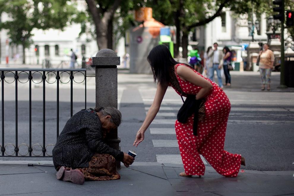 15.HISZPANIA, Madryt, 9 czerwca 2012: Kobieta wrzuca drobne żebrzącej staruszce. (Foto: Pablo Blazquez Dominguez/Getty Images)