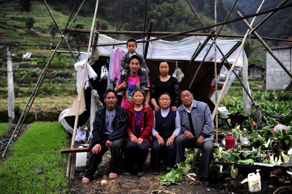 17.CHINY, Ya'an, 21 kwietnia 2013: Portret rodziny na tle szłasu, tymczasowego miejsca zamieszkania.  AFP PHOTO