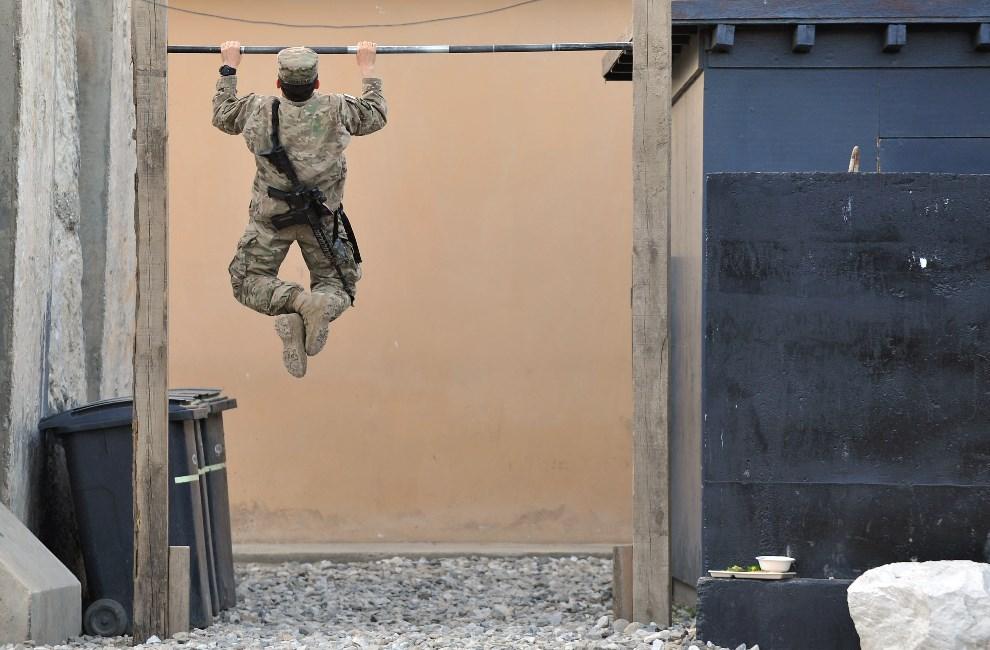 18.AFGANISTAN, Watahpur District, 18 kwietnia 2013: Amerykański żołnierz podciąga się na drążku. AFP PHOTO / MANJUNATH KIRAN