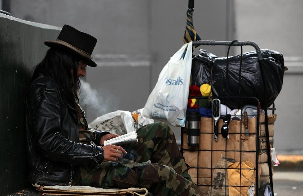 19.USA, San Francisco, 25 stycznia 2010: Bezdomny o imieniu Joe, czyta książkę siedząc na ulicy. (Foto: Justin Sullivan/Getty Images)