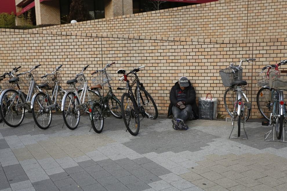 20.JAPONIA, Tokio, 7 lutego 2013: Bezdomny siedzący między zaparkowanymi rowerami. (Foto: Ken Ishii/Getty Images)